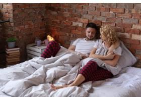 一对躺在床上拥抱的夫妇_9108373