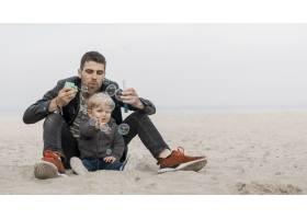 与儿子和爸爸在海滩上的快乐时刻_7732318