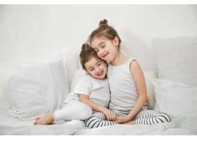 两个可爱的小女孩依偎在卧室的床上_8945639