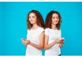两个女人双胞胎微笑着看着蓝色上面的手机_9029449