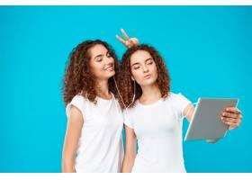 两个女人的双胞胎在平板电脑上自拍上面是_9029272
