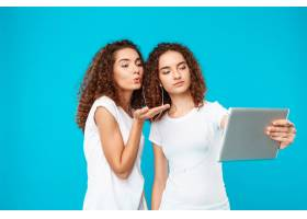 两个女人的双胞胎在平板电脑上自拍上面是_9029275