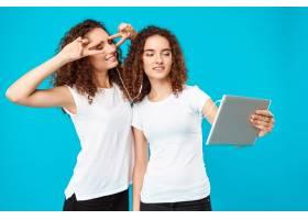 两个女人的双胞胎在平板电脑上自拍上面是_9029277