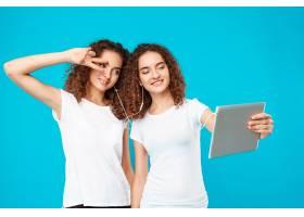 两个女人的双胞胎在平板电脑上自拍上面是_9029279