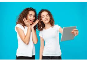 两个女人的双胞胎在平板电脑上自拍上面是_9029280
