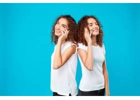 两个女人的双胞胎在电话里交谈脸上露出蓝_9029439