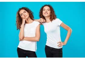 两个女人的双胞胎在蓝色上方摆姿势一个不_9029395
