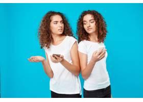 两个女人的双胞胎在蓝色上方看手机_9029447