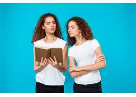 两个女人的双胞胎在蓝色上面看书_9029385