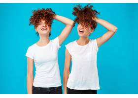 两个女人的双胞胎抱着头发在蓝色上开玩笑_9029371