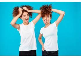 两个女人的双胞胎抱着头发在蓝色上开玩笑_9029384