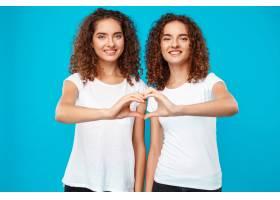 两个女人的双胞胎用手盖着蓝色展示了自己的_9029421