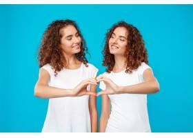 两个女人的双胞胎用手盖着蓝色展示了自己的_9029423