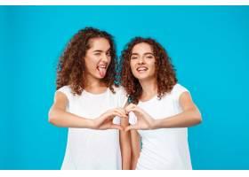 两个女人的双胞胎用手盖着蓝色展示了自己的_9029426
