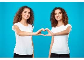 两个女人的双胞胎用手盖着蓝色展示了自己的_9029429