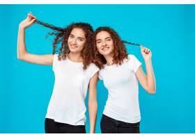 两个女人的双胞胎留着头发在蓝色上微笑_9029402