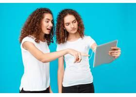 两个女人的双胞胎看着平板电脑惊讶得目瞪_9029284