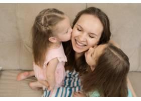 两个女儿在亲吻她们的妈妈_8965586