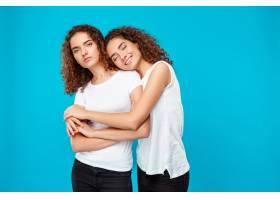 两个年轻女子双胞胎拥抱在一起笑容满面_9029345