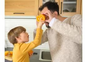 一个孩子为他的父亲拿着半个橙子_7771054