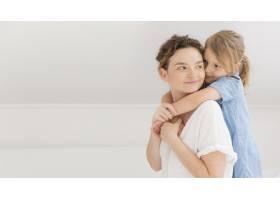 一个年轻的女孩在家里拥抱她的妈妈_7936883