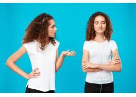一名妇女对戴着蓝色耳机的双胞胎妹妹怨恨不_9029289