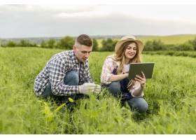 一对夫妇拿着平板电脑在农场工作_8763040