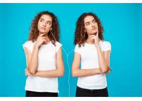 一对双胞胎戴着耳机听音乐想着蓝色_9029261