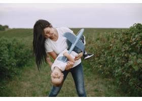 母亲带着小儿子玩玩具飞机_9696267