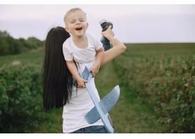 母亲带着小儿子玩玩具飞机_9696270