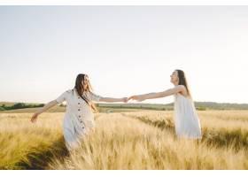 田野里两个穿着白色连衣裙留着长发的姐妹_9658854