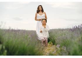 母亲带着年幼的女儿在薰衣草地里美丽的女_10065158