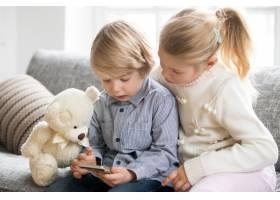 男孩和女孩坐在沙发上一起使用智能手机_3953877