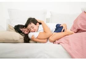 深色头发的母亲睡在沙发上抱着可爱的儿子_9988316