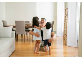 笑着的父亲在家里拥抱可爱的小孩子_9988566