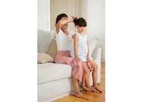 漂亮妈妈坐在沙发上为可爱的女孩做发型_9988603