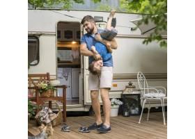 父亲和儿子在大篷车旁玩耍_9943081