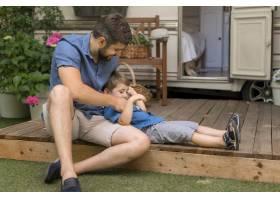 父亲在他们的大篷车旁拥抱他的儿子_9943084
