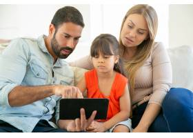 父母和可爱的女孩坐在沙发上一起使用平板_9988585