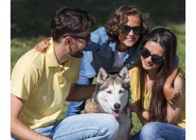 父母和孩子在公园与狗共度时光_9860960