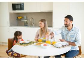 父母夫妇和女孩一起吃早餐坐在餐桌旁端_9988589