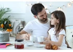 爸爸和女儿在厨房吃早餐_9931308