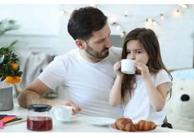 爸爸和女儿在厨房吃早餐_9931309