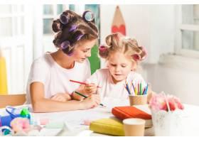 这位年轻的母亲和她的小女儿在家里用铅笔作_9902261