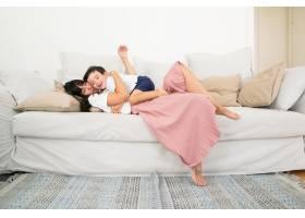 高加索母亲躺在沙发上抱着小儿子和孩子_9988332
