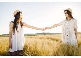 田野里两个穿着白色连衣裙留着长发的姐妹_9658838