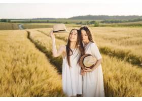 田野里两个穿着白色连衣裙留着长发的姐妹_9658842