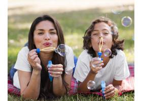 母亲和孩子一起在户外做气球_9860906