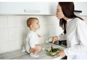 母亲在准备食物而婴儿则坐在柜台上_9696749