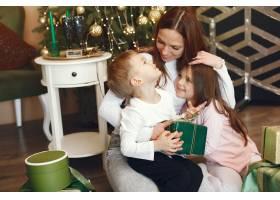 母亲在圣诞树附近带着可爱的孩子_9659183